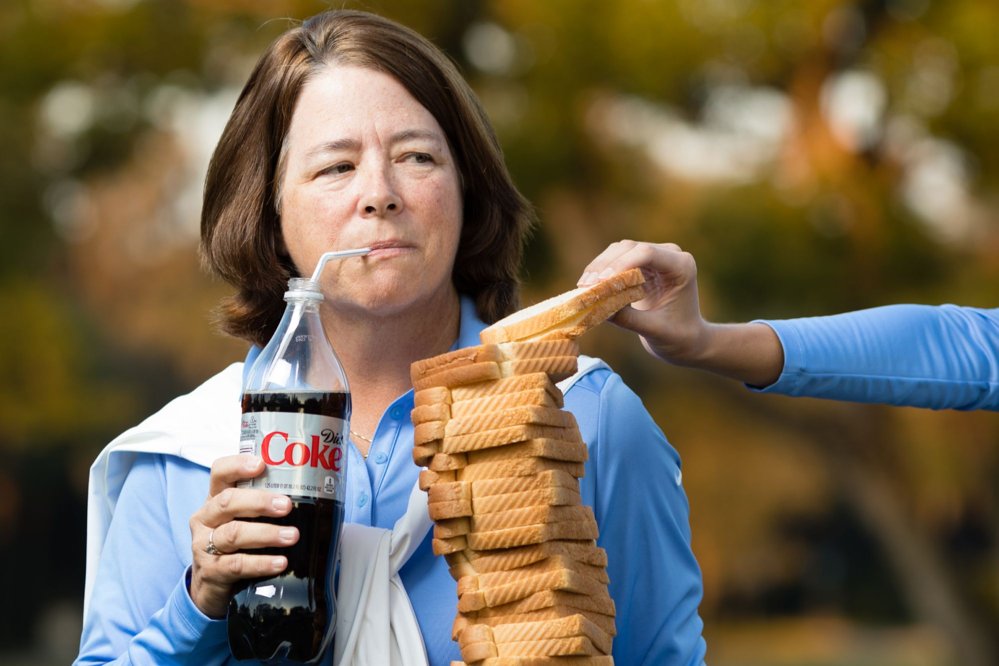 Julie Garner holding a stack of white bread and a diet Coke.
