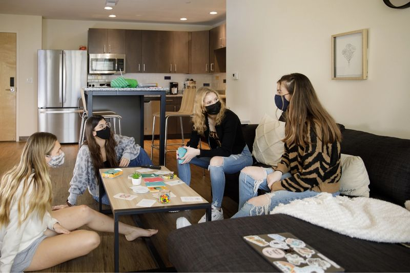 Four female students socializing in the living room of their dorm at Lakeside.