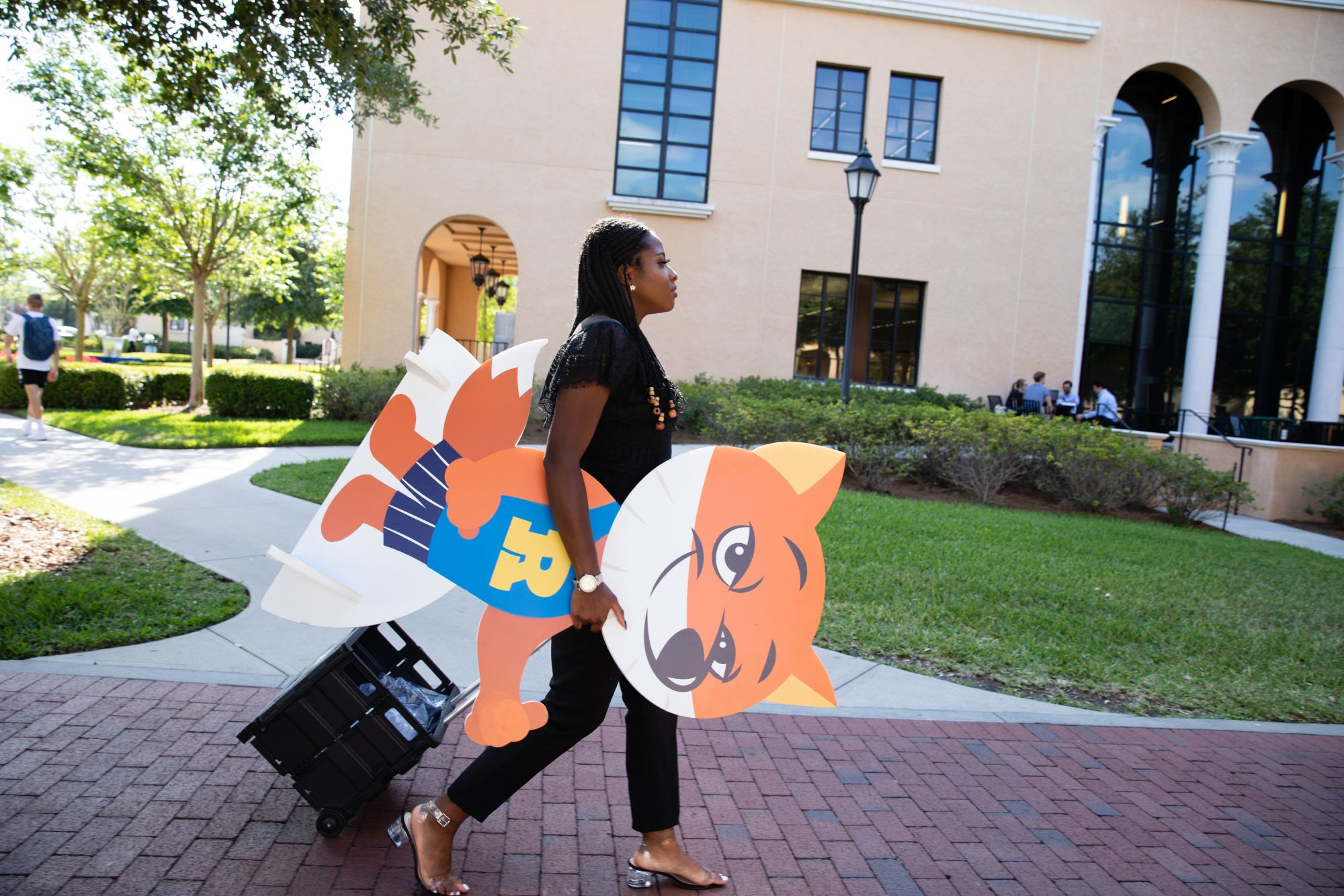 Happiness Omochere '20 carrying a cardboard fox cutout.