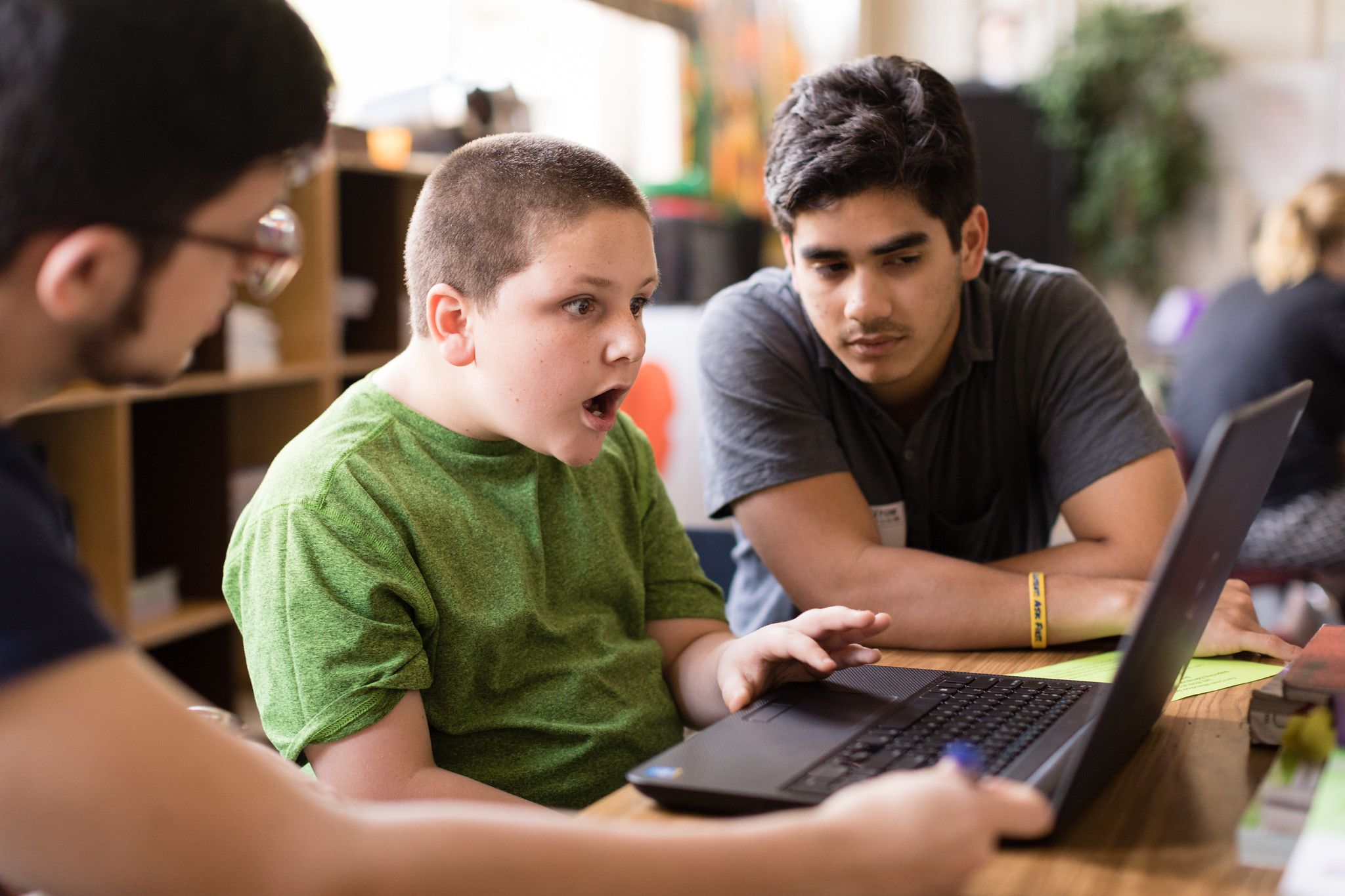 A student gets excited when he learns from Rollins students how to code a video game.
