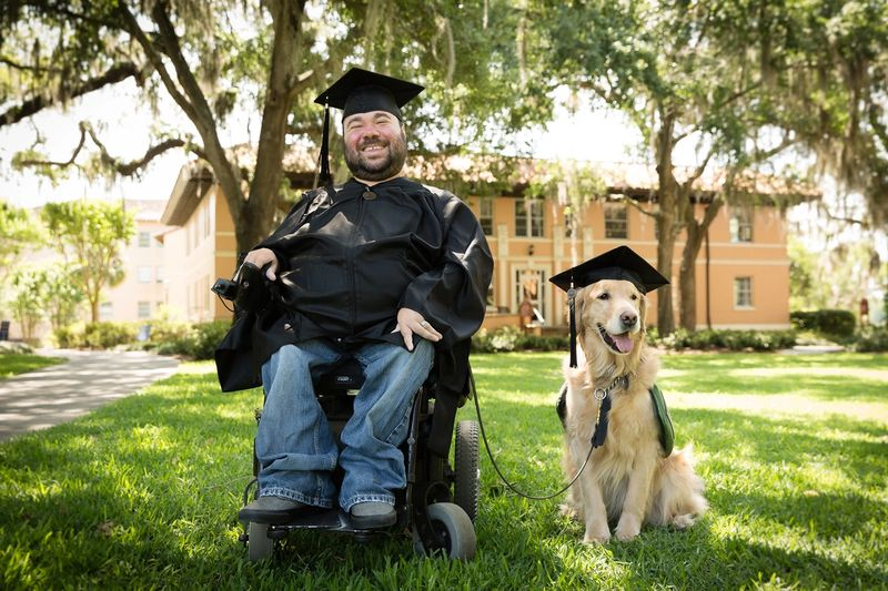 A Rollins grad poses in cap and gown alongside his service dog.