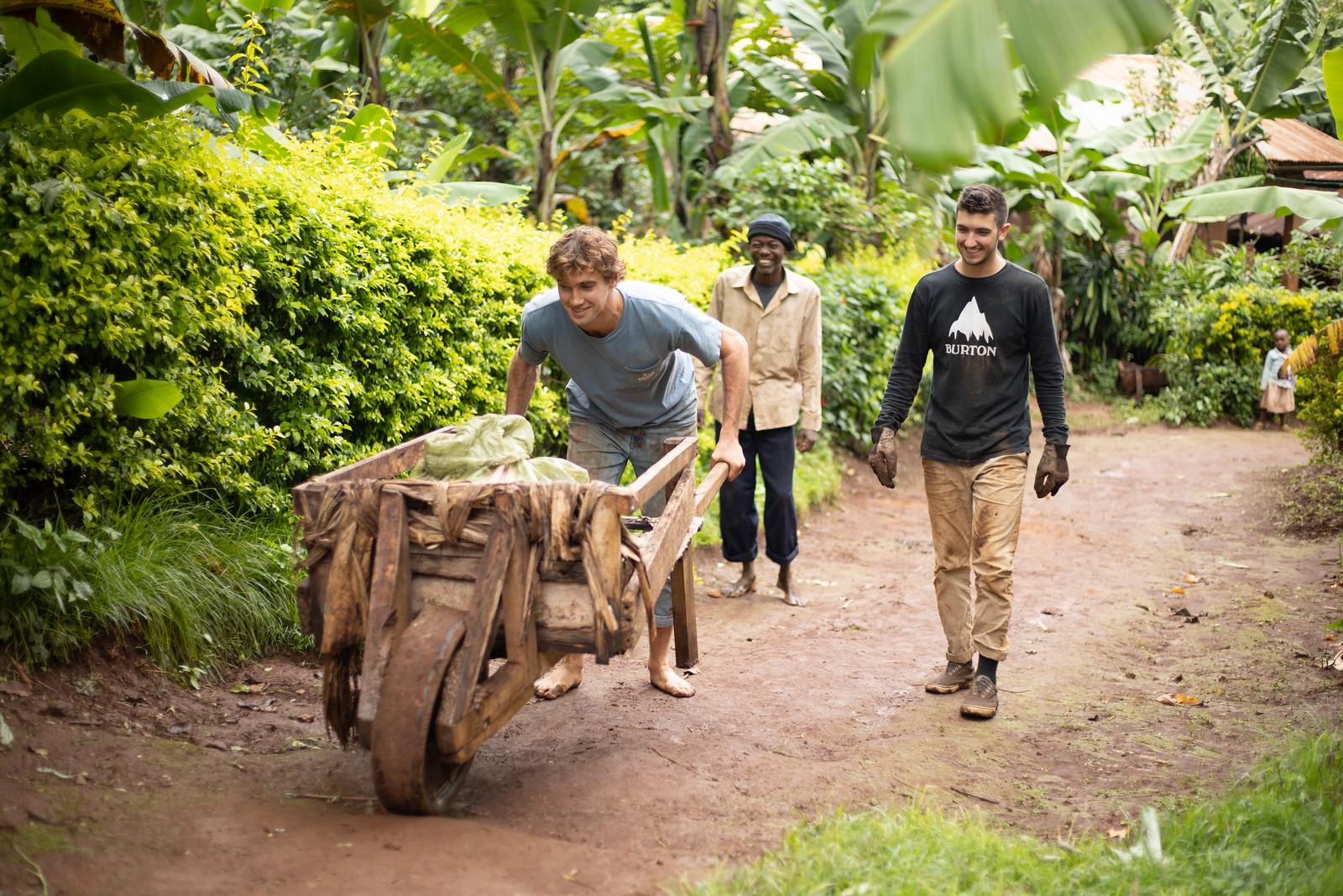 Student pushing a wheelbarrow up an incline in the village of Mkyashi, Tanzania.