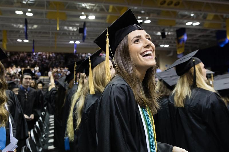 A college graduate smiles at the crowd during a commencement ceremony.