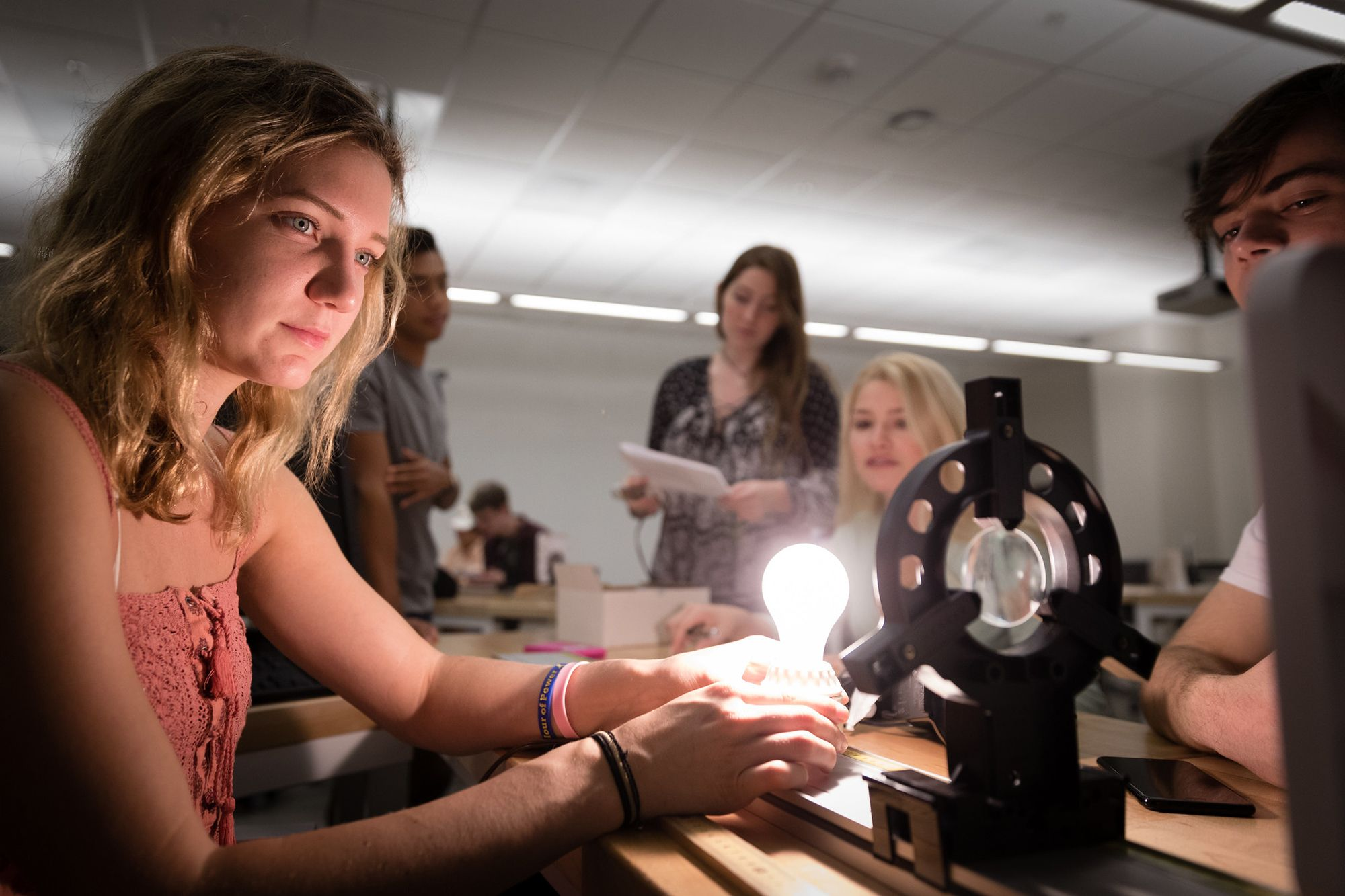 Students conduct an optics lab in a physics course.