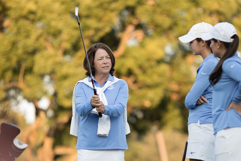 A golf coaches instructs a pair of student-athletes.