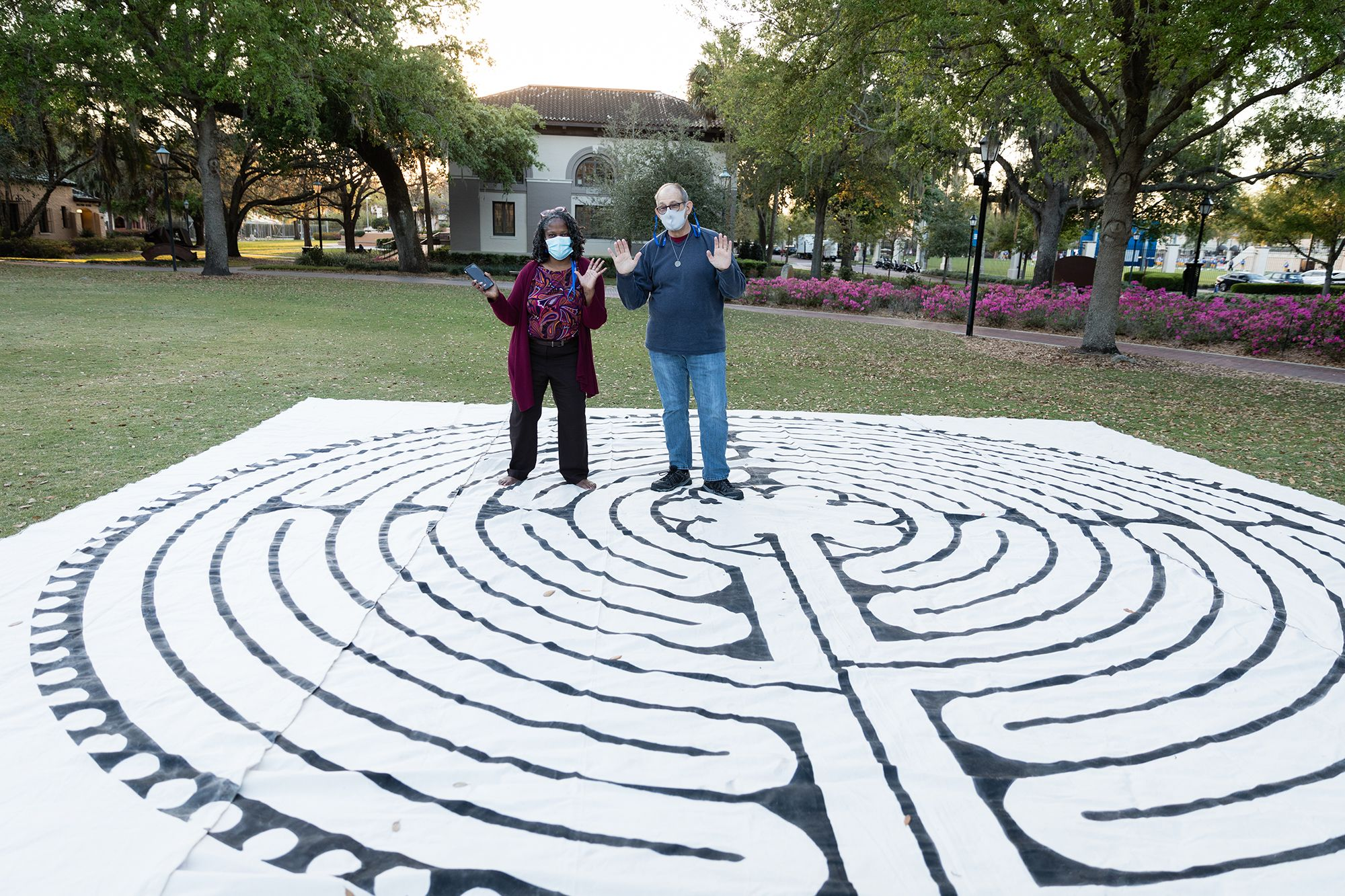 """Rev. Katrina Jenkins and Frank Faine, project coordinator of Rollins' new labyrinth, roll out the canvas labyrinth for """"Fiat Lux: An Evening of Remembrance and Hope,"""" greatly anticipating the arrival of the permanent space this fall."""