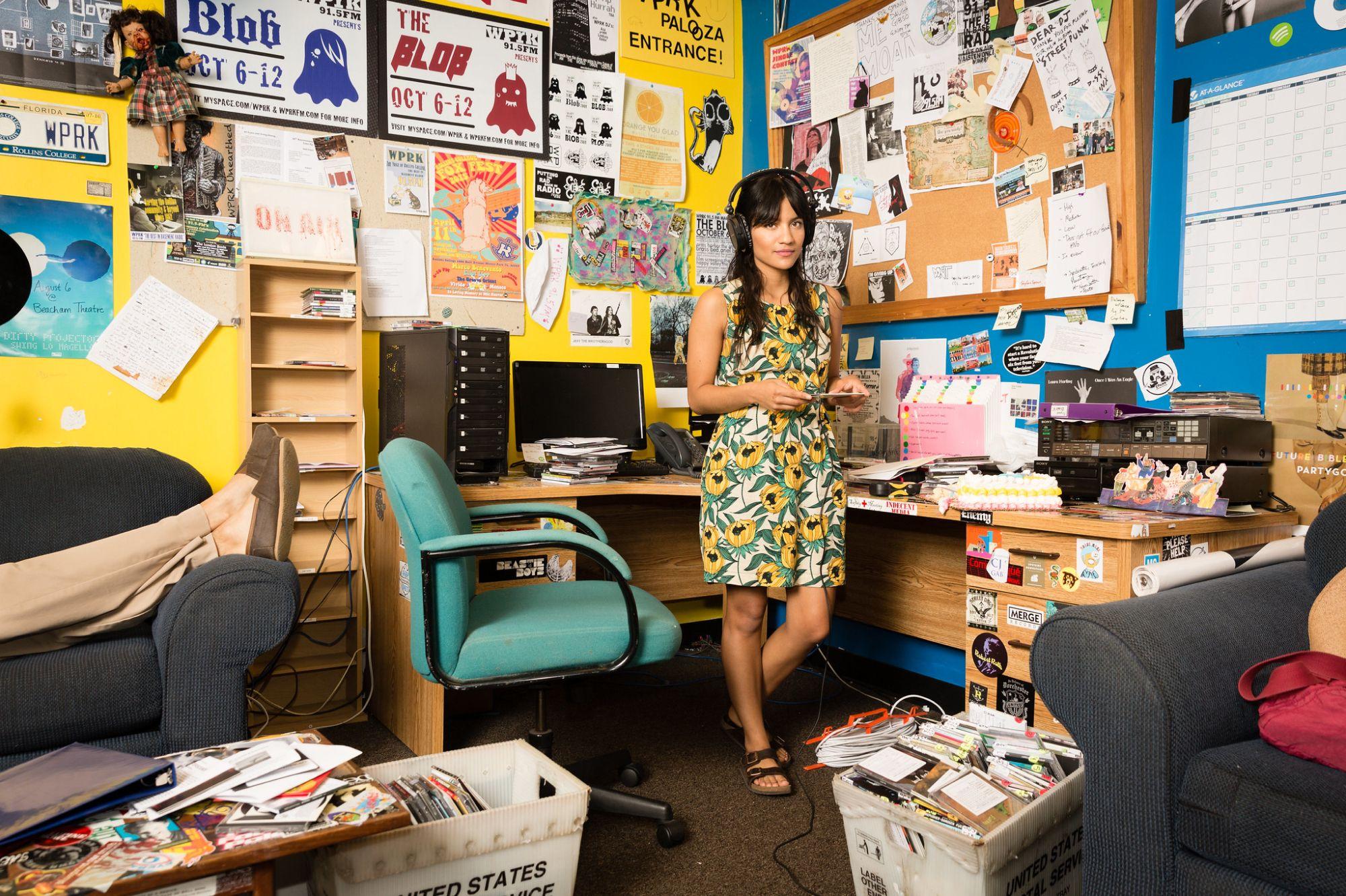 Alumn, Maria Gutierrez, standing at her desk at WPRK with headphones on.