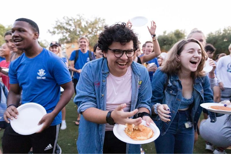 Students participate in the pancake flip during orientation week.