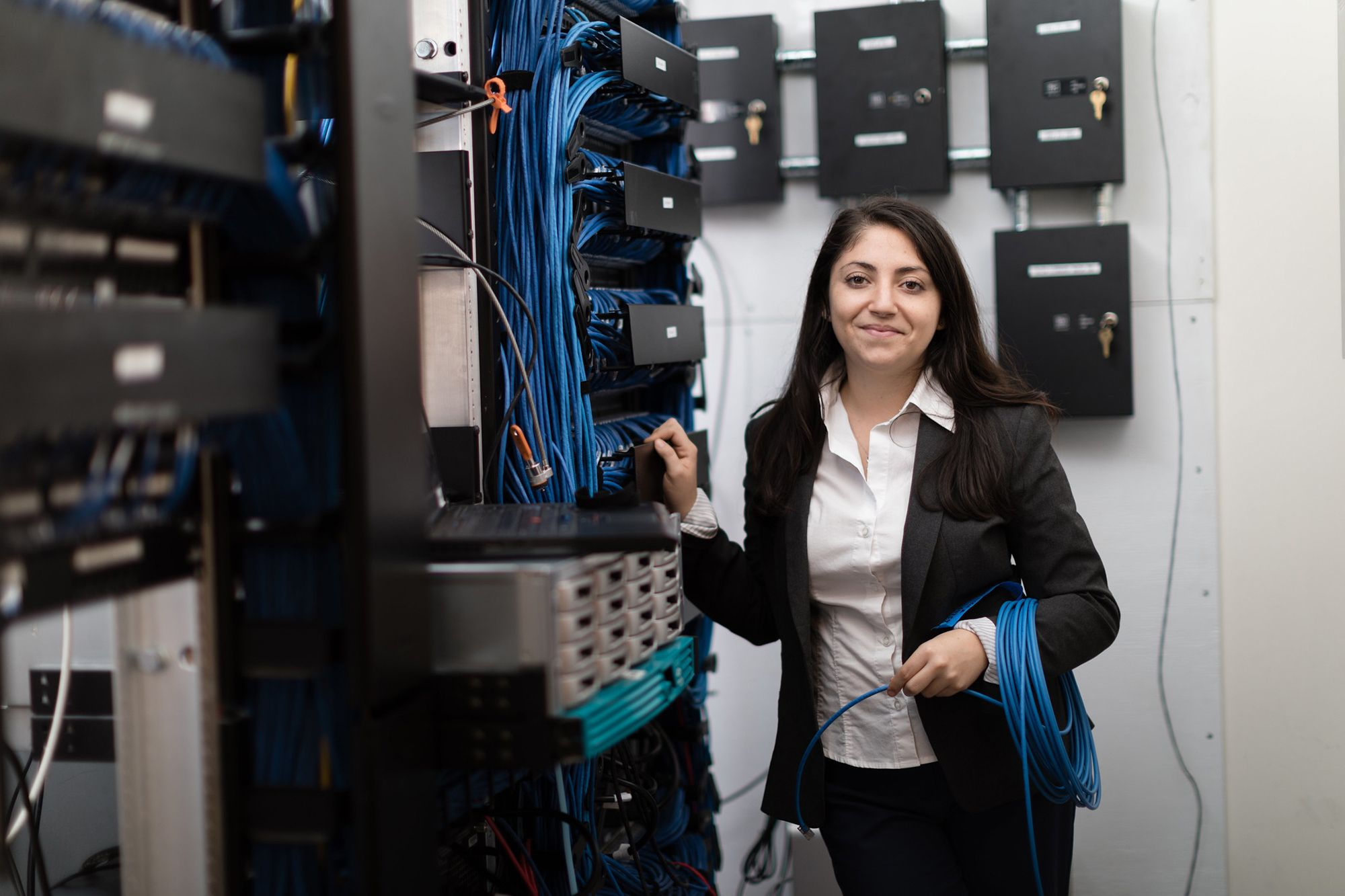 A computer science alumn standing in front of a server rack filled with switches holding blue LAN cabling.