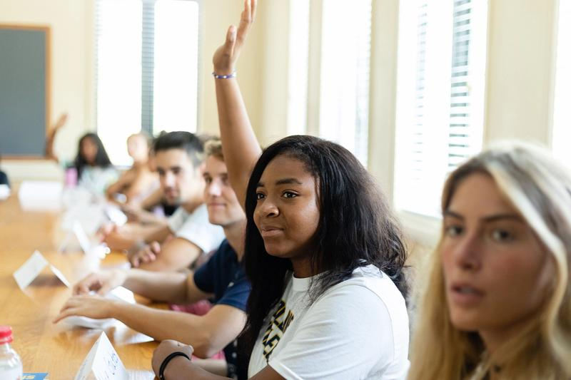 A student raises her hand to be called on during a college class.