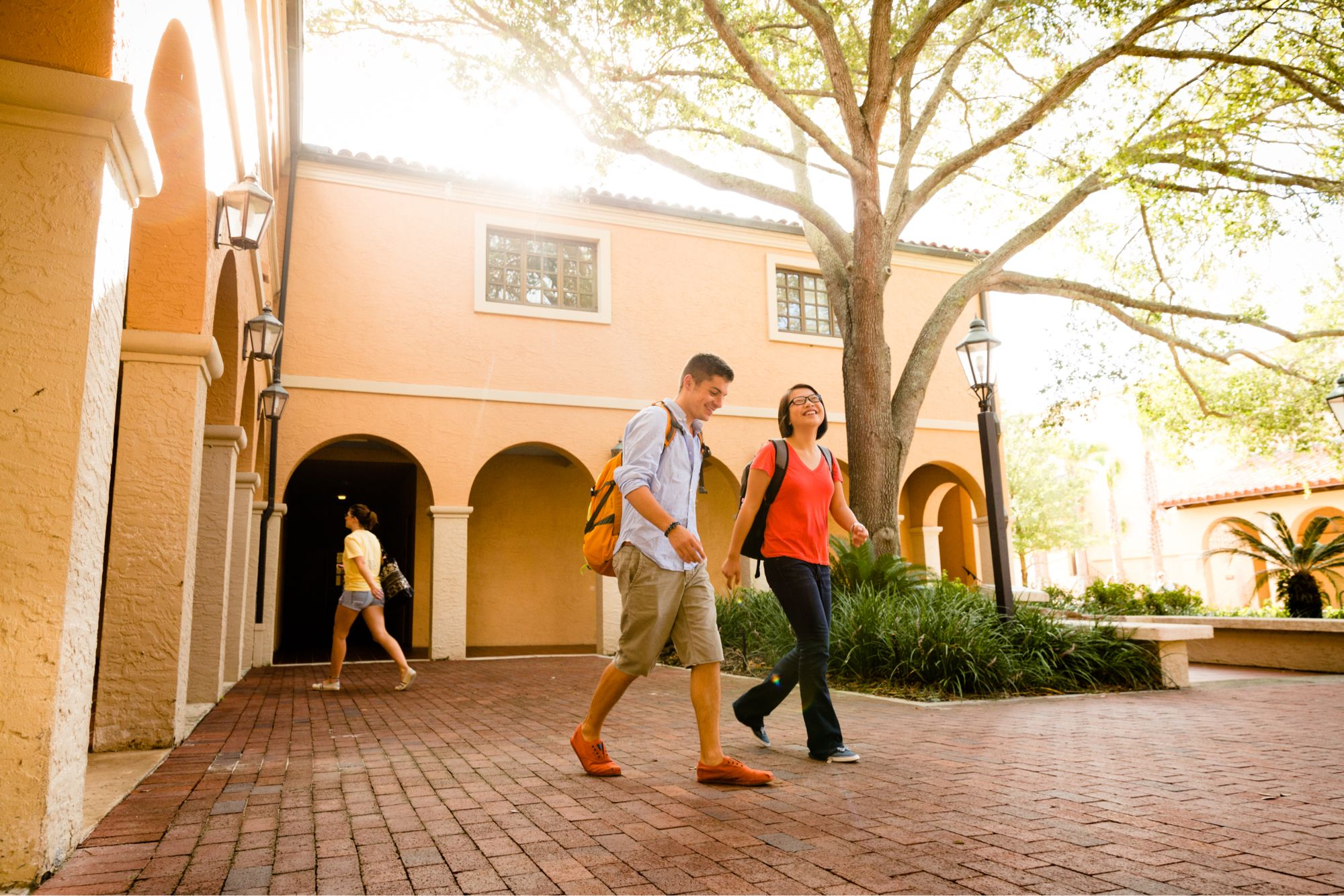 A couple of liberal arts college students walking across campus smiling.