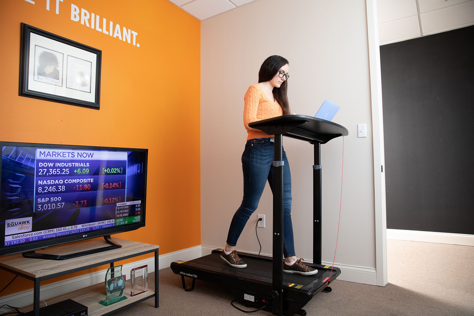 Neny Lairet '21 keeps track of the markets while on the treadmill at Knoza Consulting.