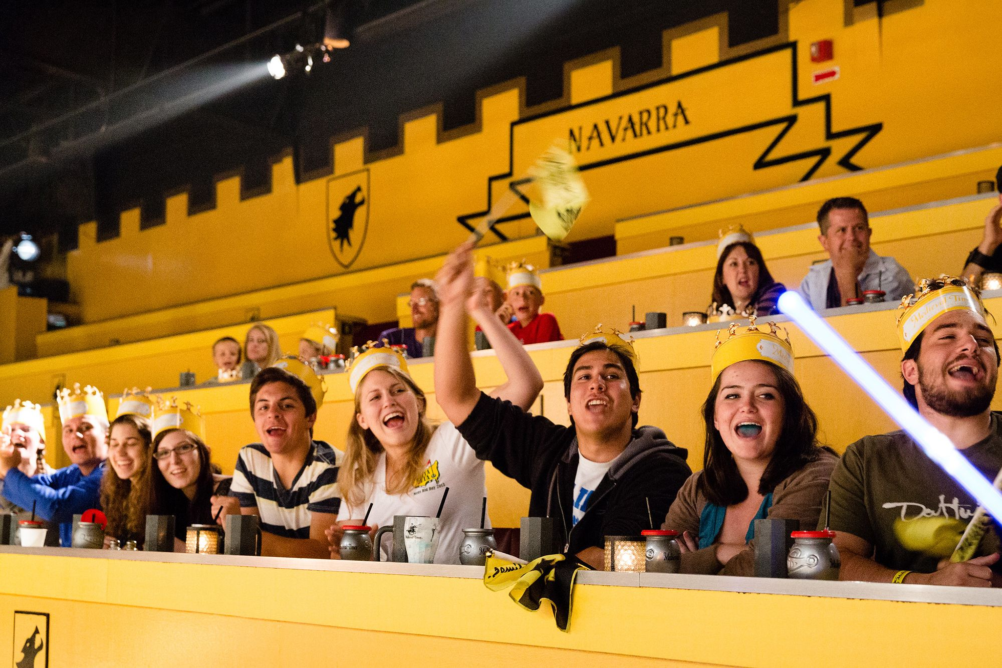 Students sitting in the bleachers at Medieval Times cheering.