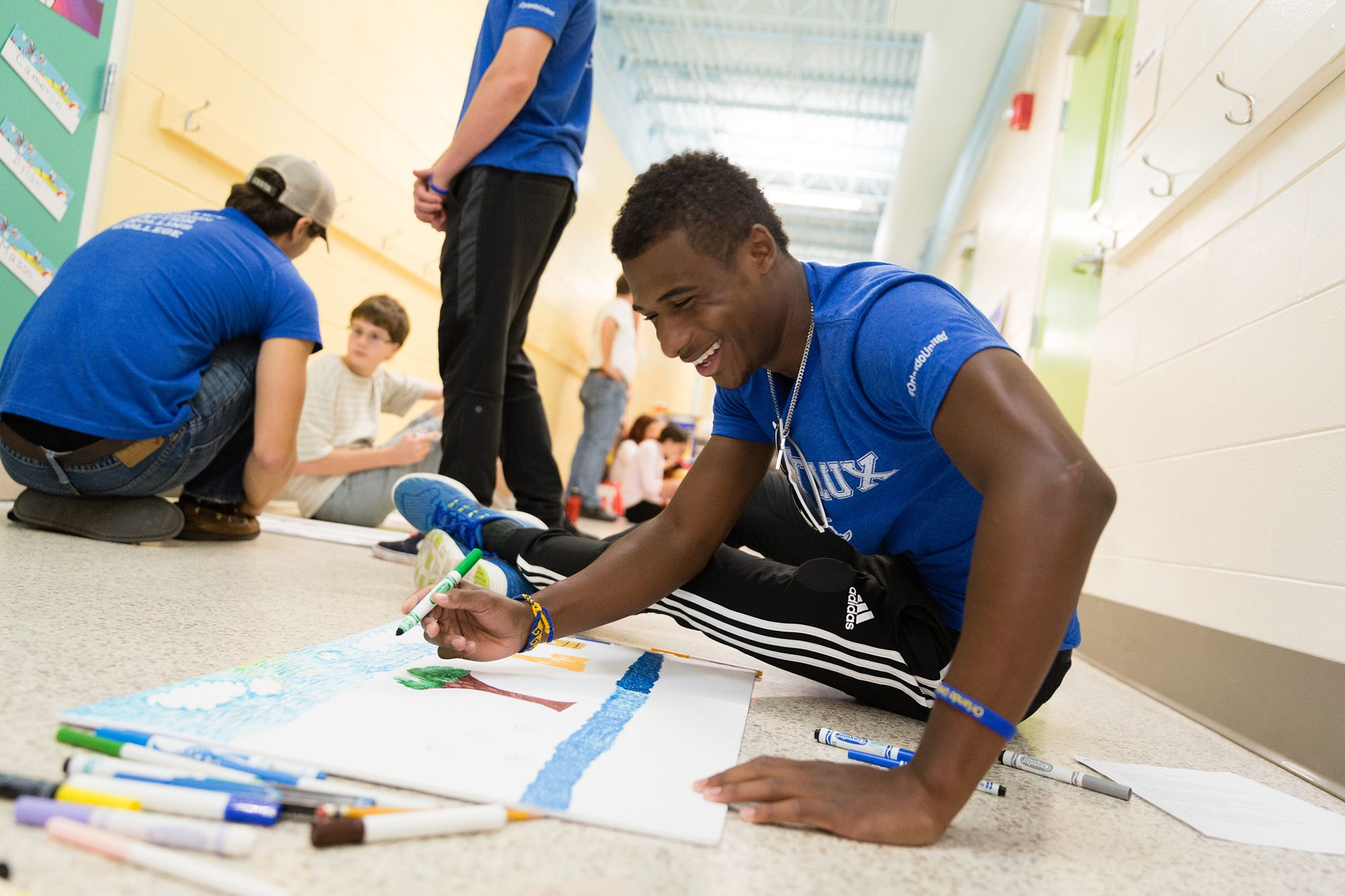 An African-American college student decorating a banner on the floor of a local Orlando elementary school.