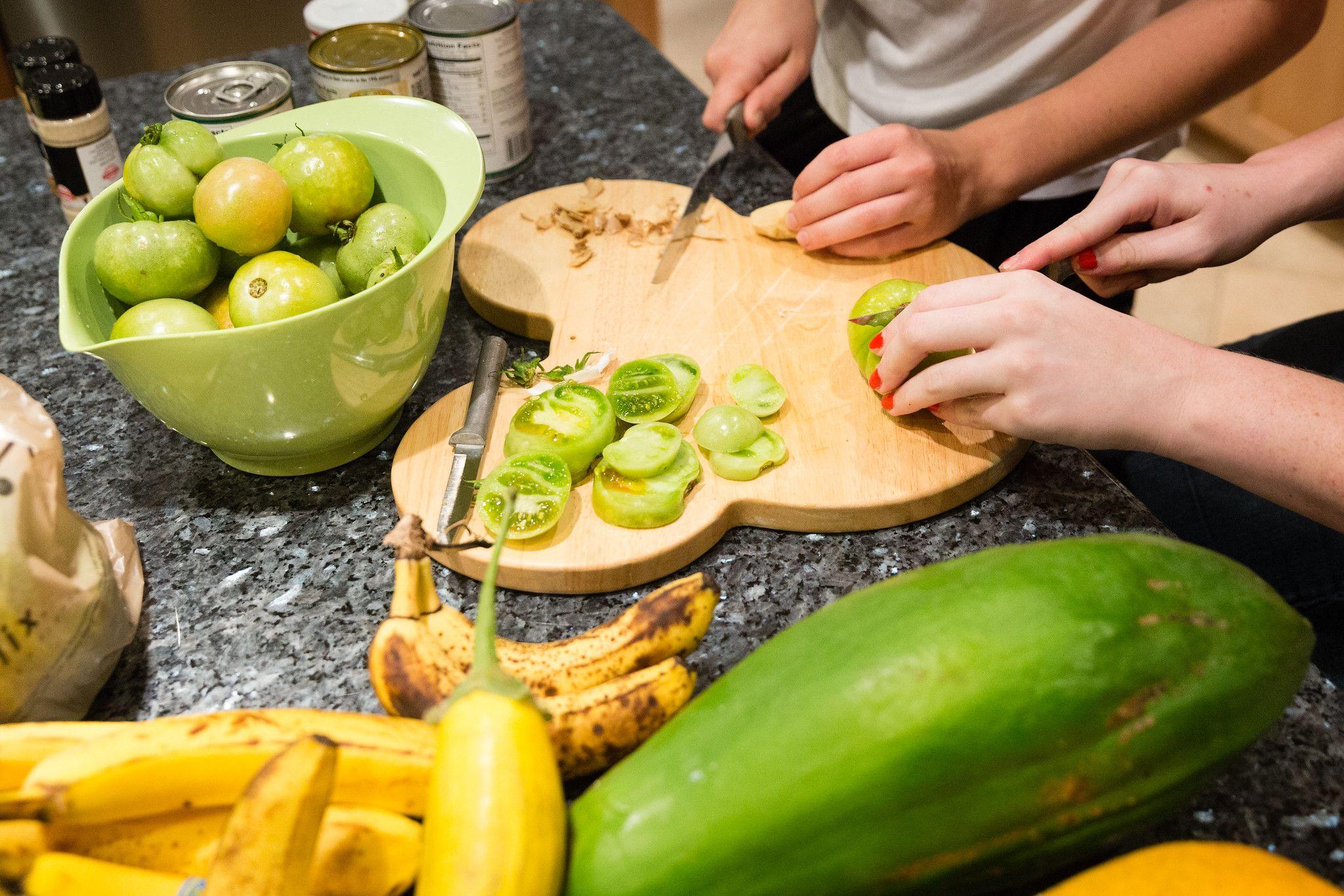 Students slice vegetables for dinner preparation.