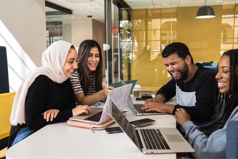 Four students at a table working together.