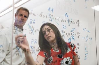 A mathematics major and a professor work out equations on a glass wall.