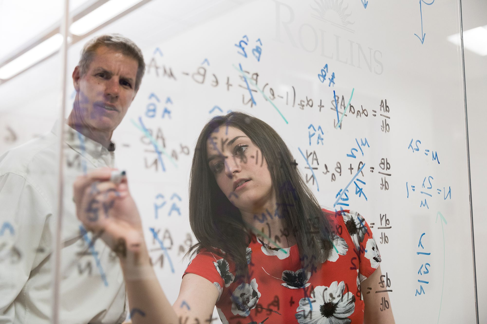 A mathematics college student writing a problem on a glass pane to show the professor.