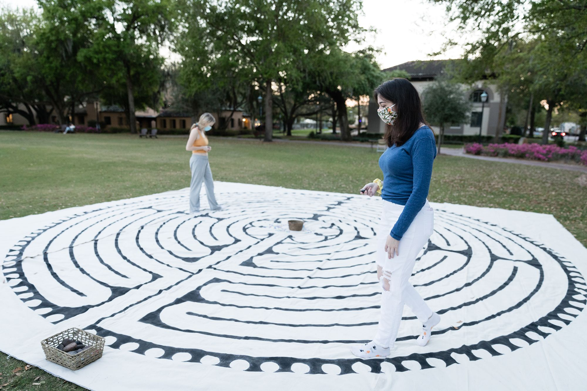 """Students engage in a canvas labyrinth walk as they reflect on one year of the pandemic during the """"Fiat Lux: An Evening of Remembrance and Hope"""" in March on Mills Lawn."""