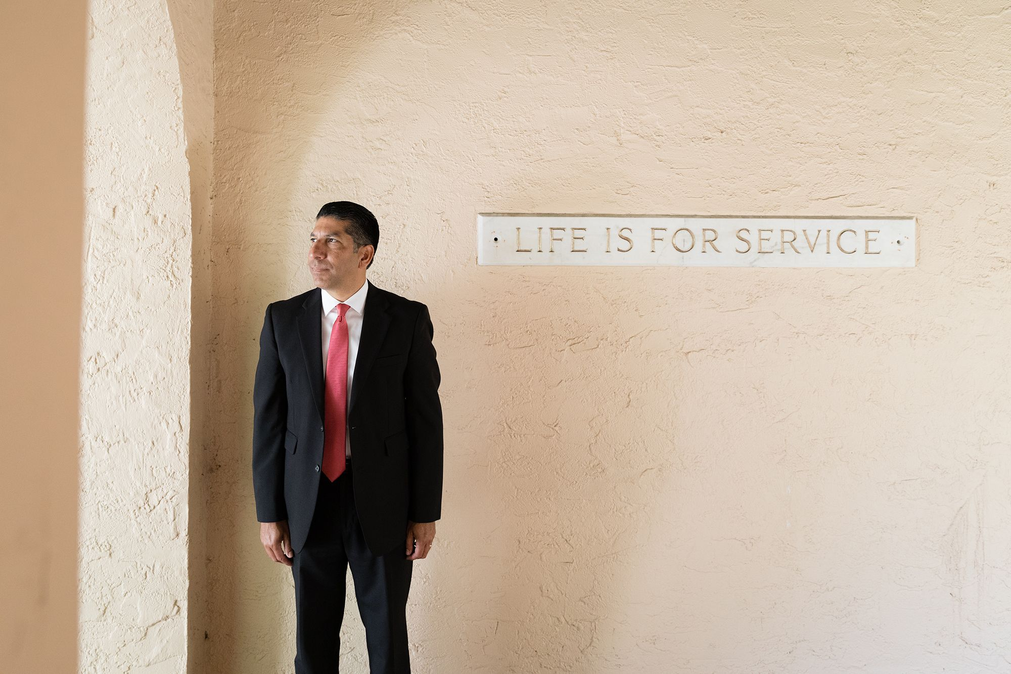 """Jose Fernandez '92 pictured in front of the """"Life is for Service"""" engraving at Rollins College."""