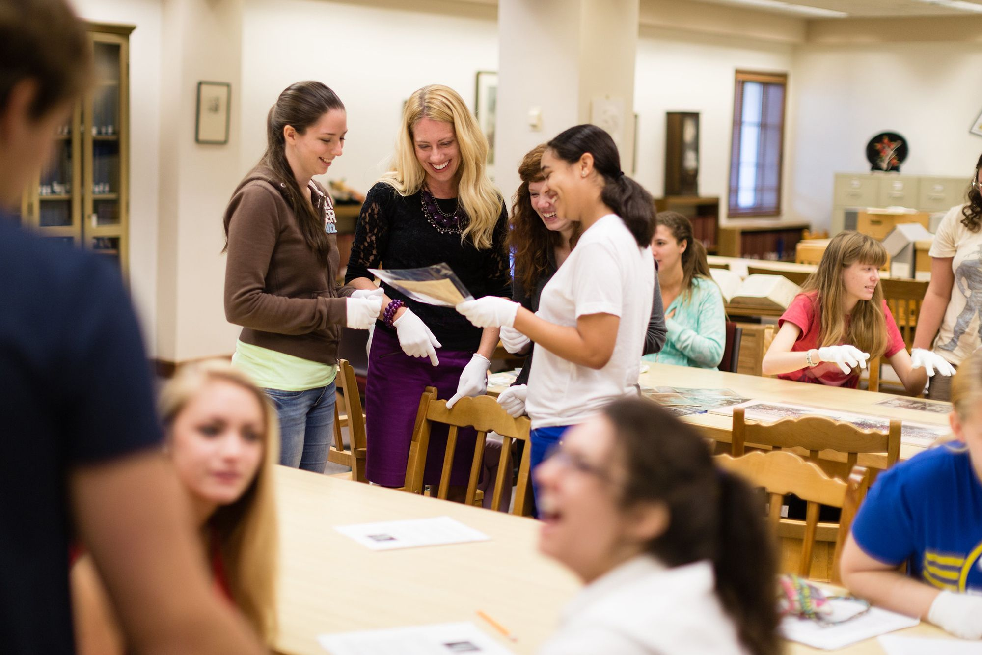 A professor and a group of students conduct research in the Olin Library archives.