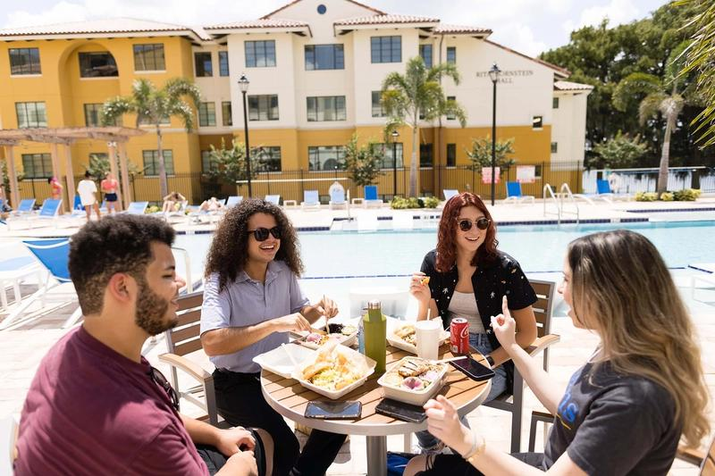 Four students share lunch on a pool deck at Rollins College.