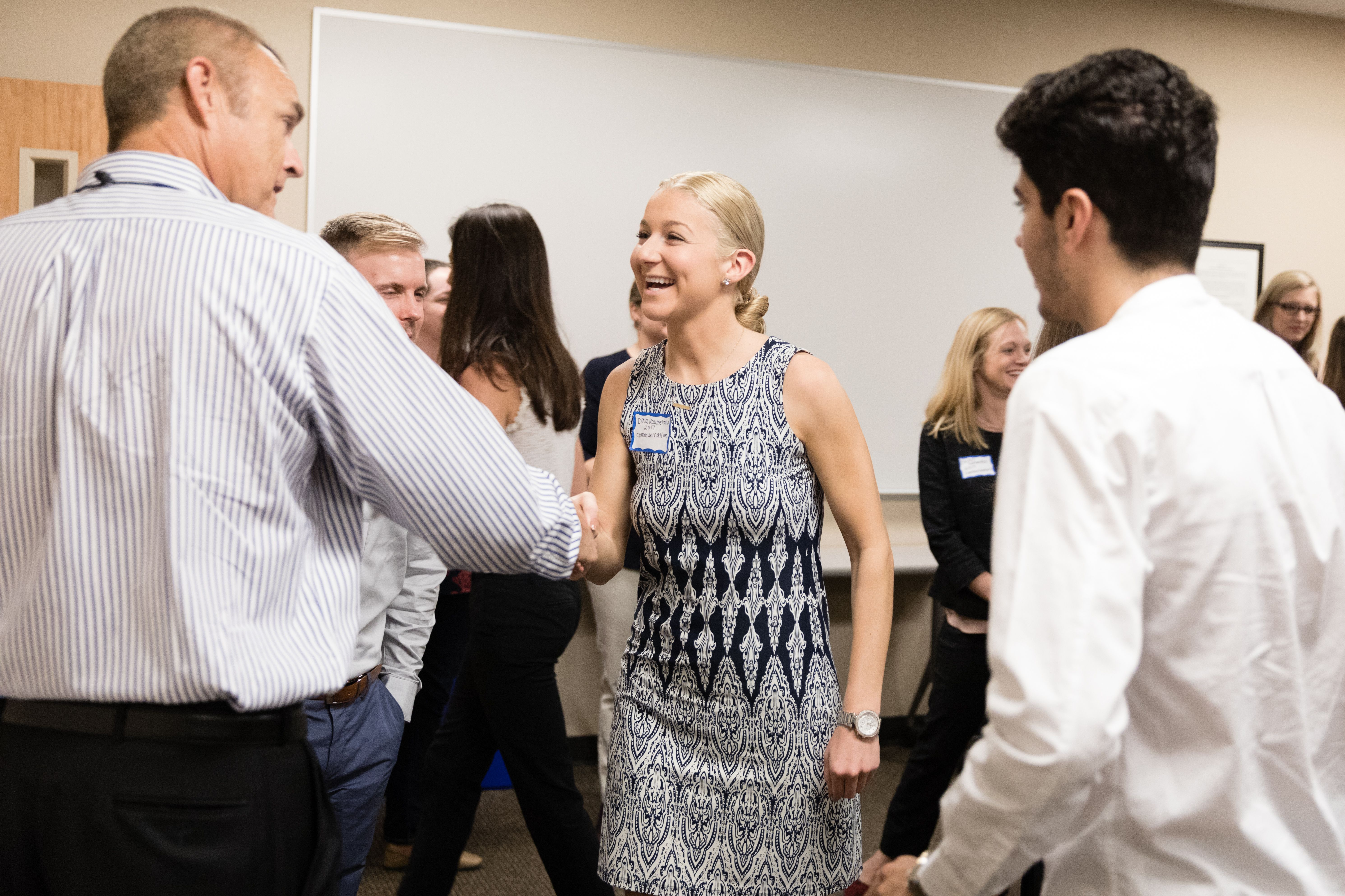 A college student greeting the CEO of a local company.