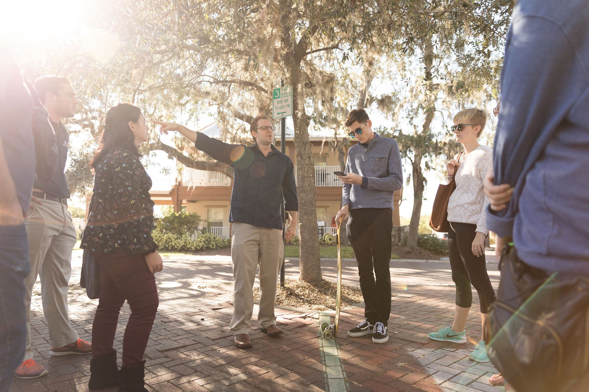 Professor Dan Myers standing on a brick sidewalk pointing to a point of interest while leading students on a digital tour.