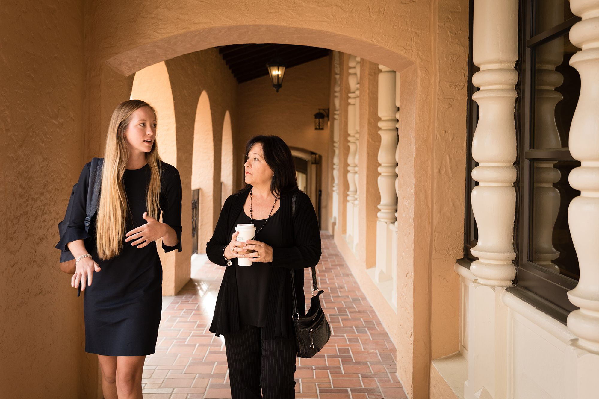 A professor and student walking together down the arched hallways of Rollins College.