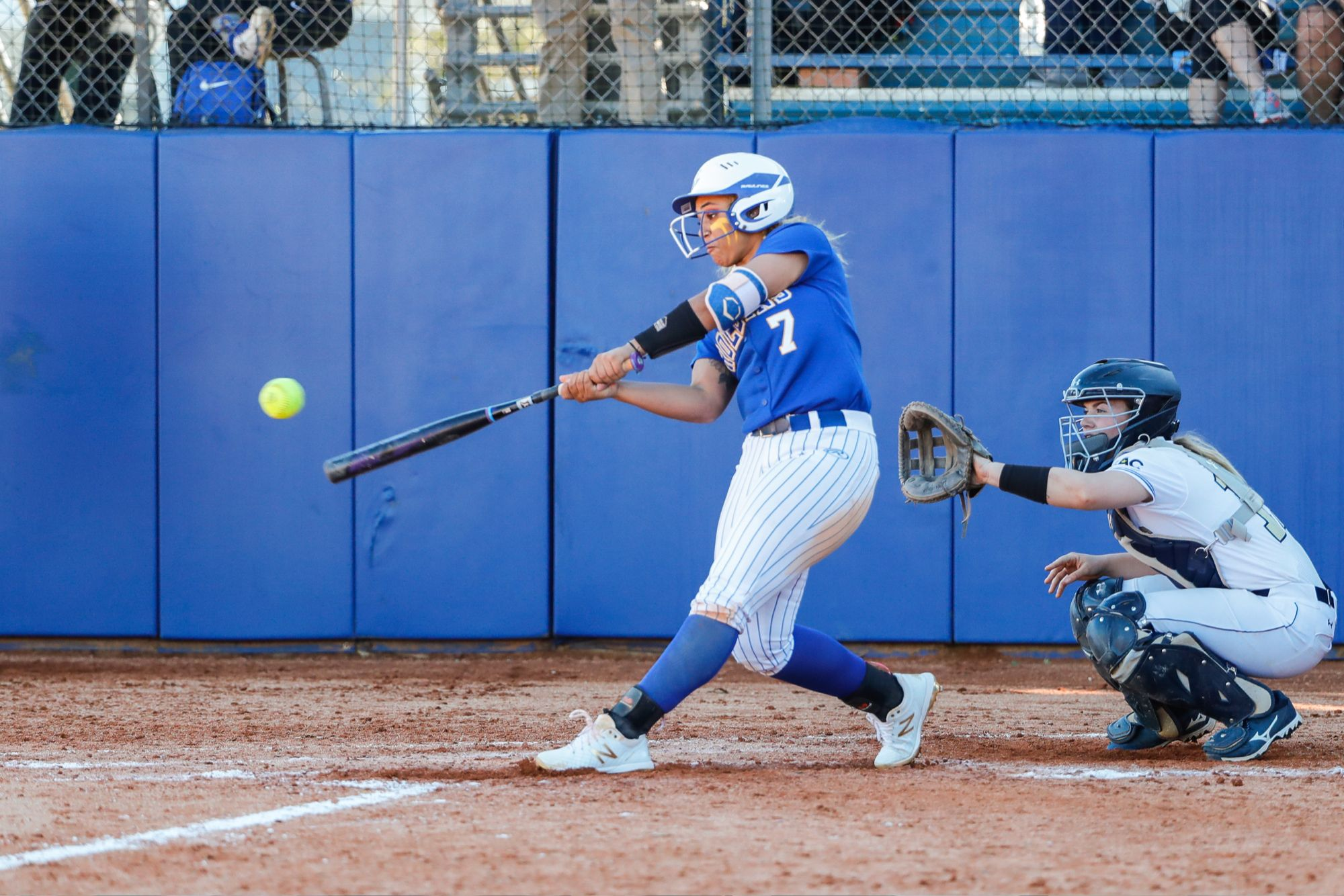 A softball player swinging and hitting a pitch over home plate.
