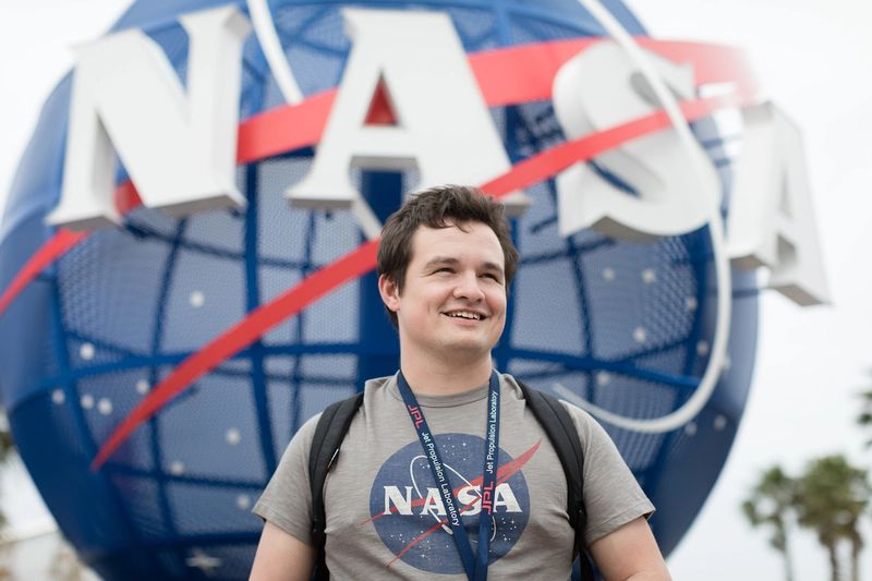 A student poses in front of a NASA sign at Kennedy Space Center.