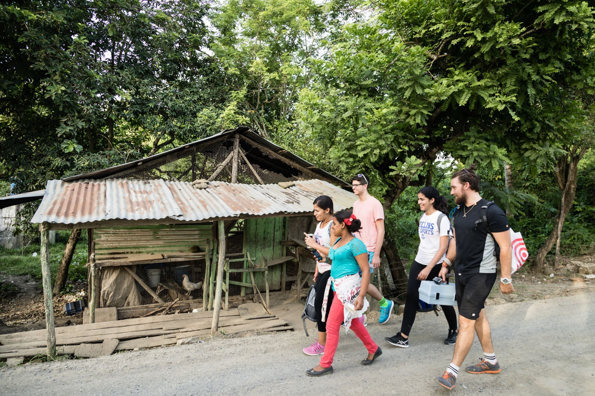 A group of students walk down a rural road during a study abroad experience in the Dominican Republic.
