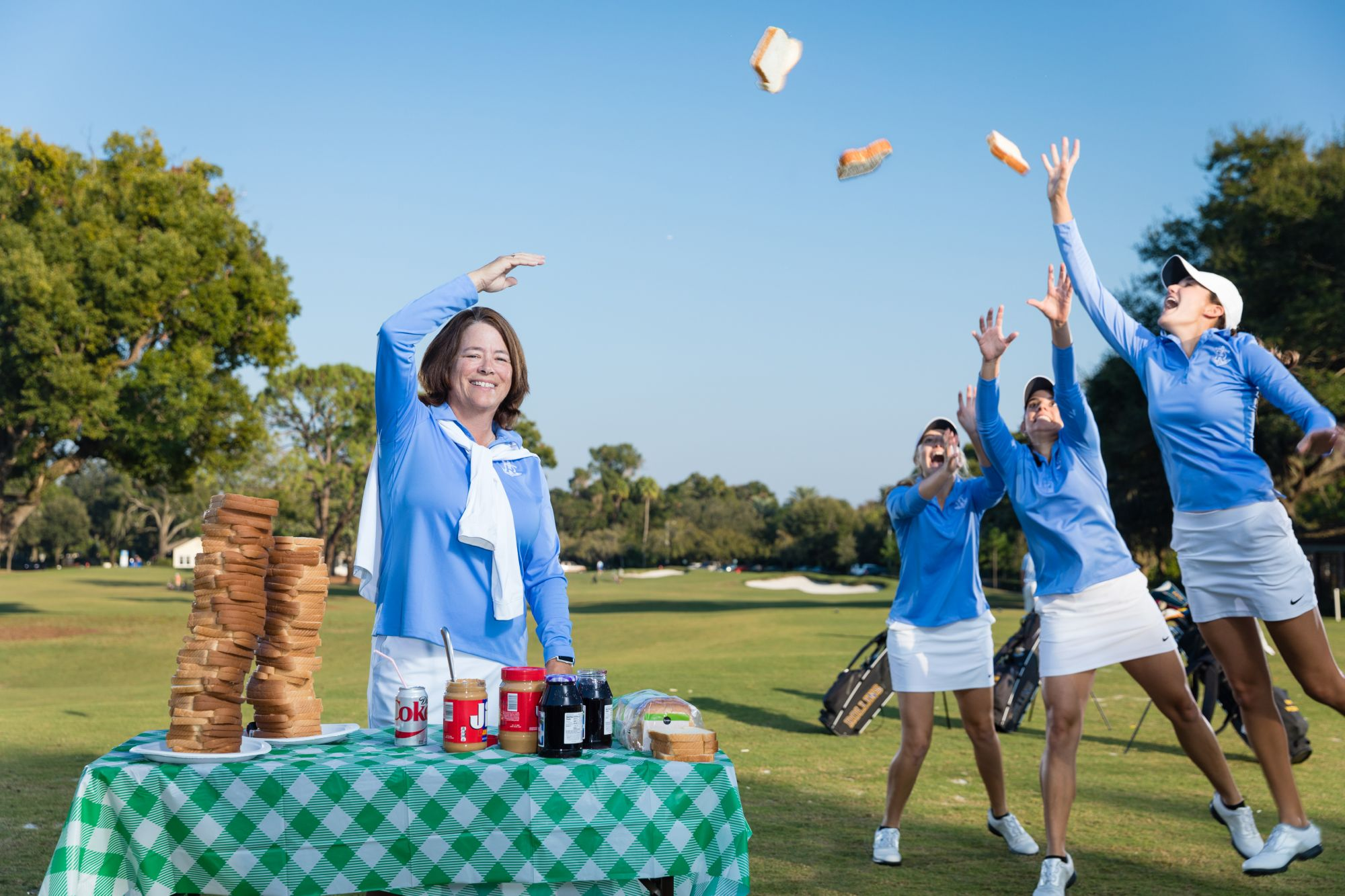 Coach Julie Garner throws sandwiches to the Rollins women's golf team.