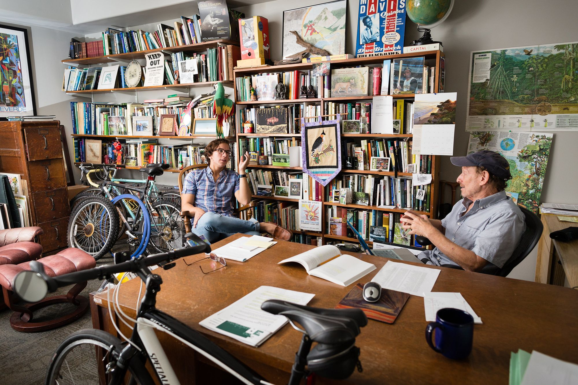 A college professor and graduate student talking in his book and bike filled office.