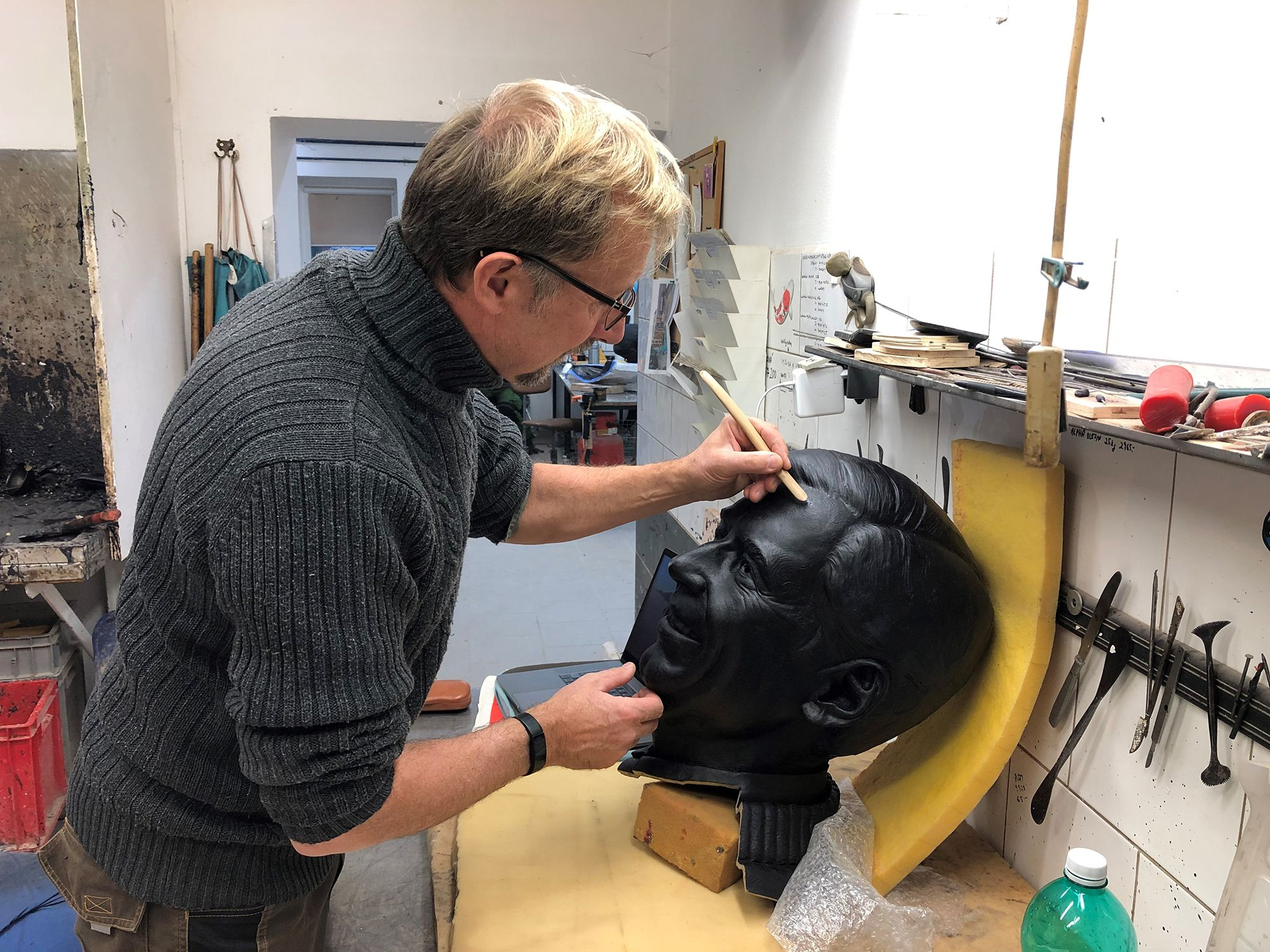 Artist Paul Day working on the head portion of the sculpture of Fred Rogers.