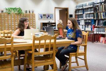 A student and a professor conduct research focused on women's studies.