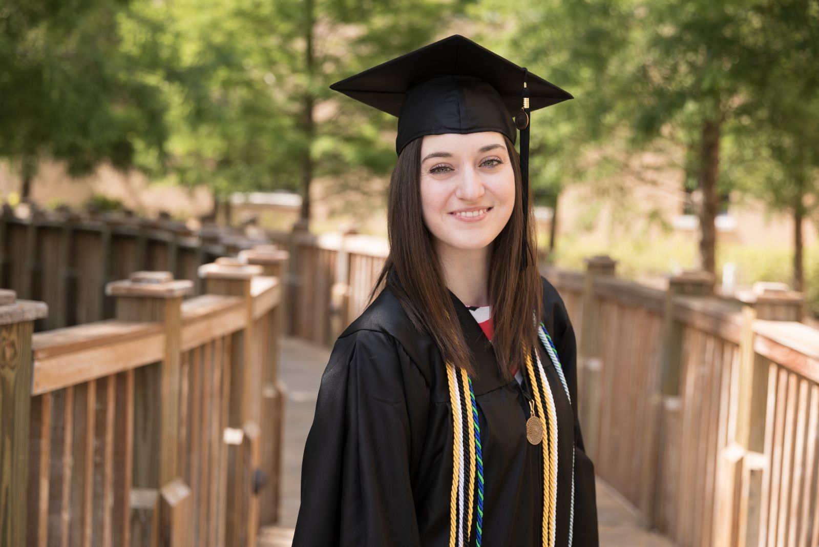 A female college student poses in a cap and gown on campus.