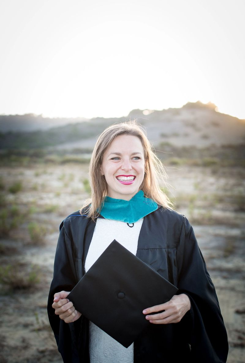Brenna McKee '15 pictured with her diploma in a desert scene.