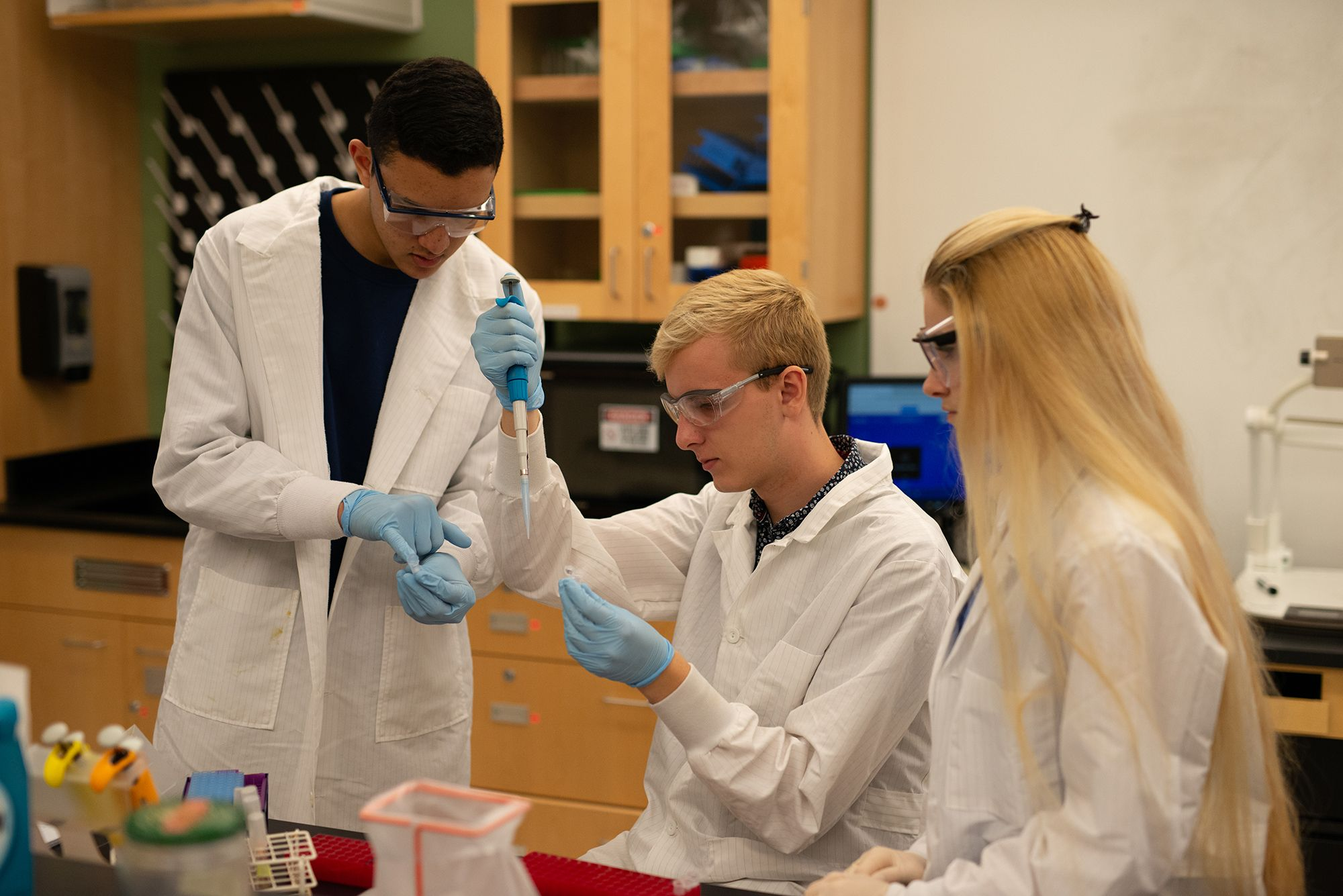 Students with lab coats, gloves, and protective goggles use a dropper to take samples.