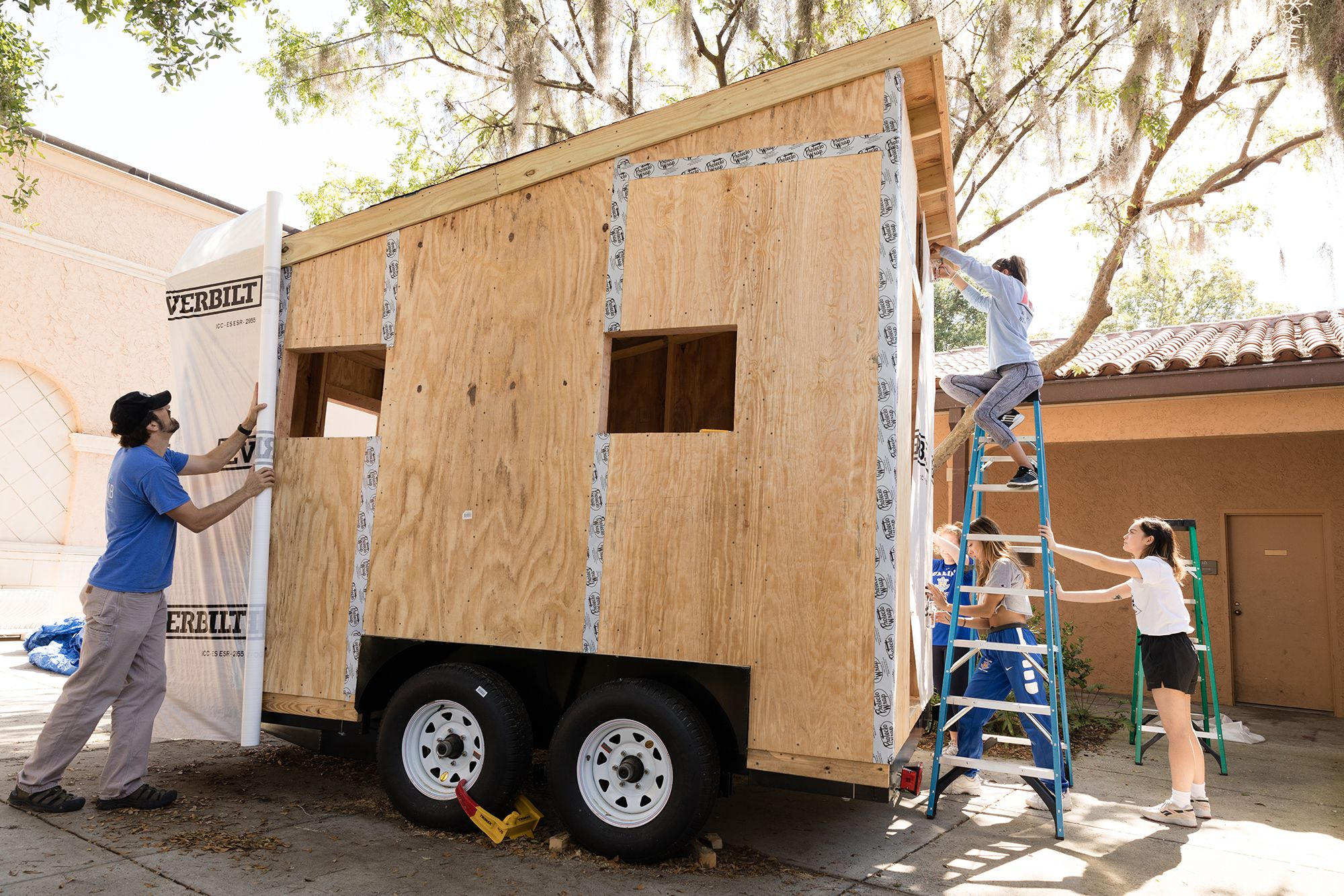Liberal arts college students wrapping a tiny home with water proofing.