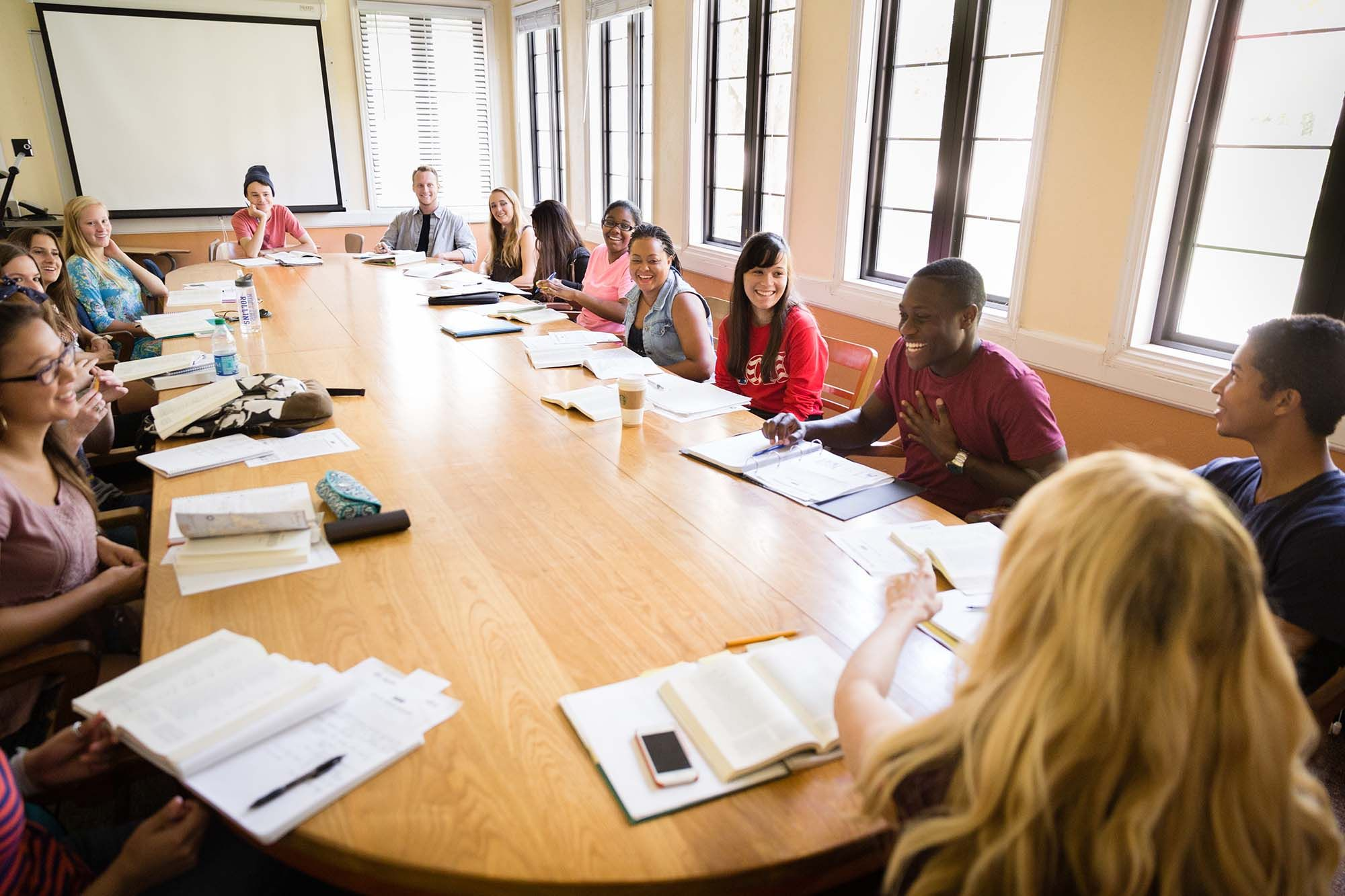 Students gather around a table during a seminar-style class session.