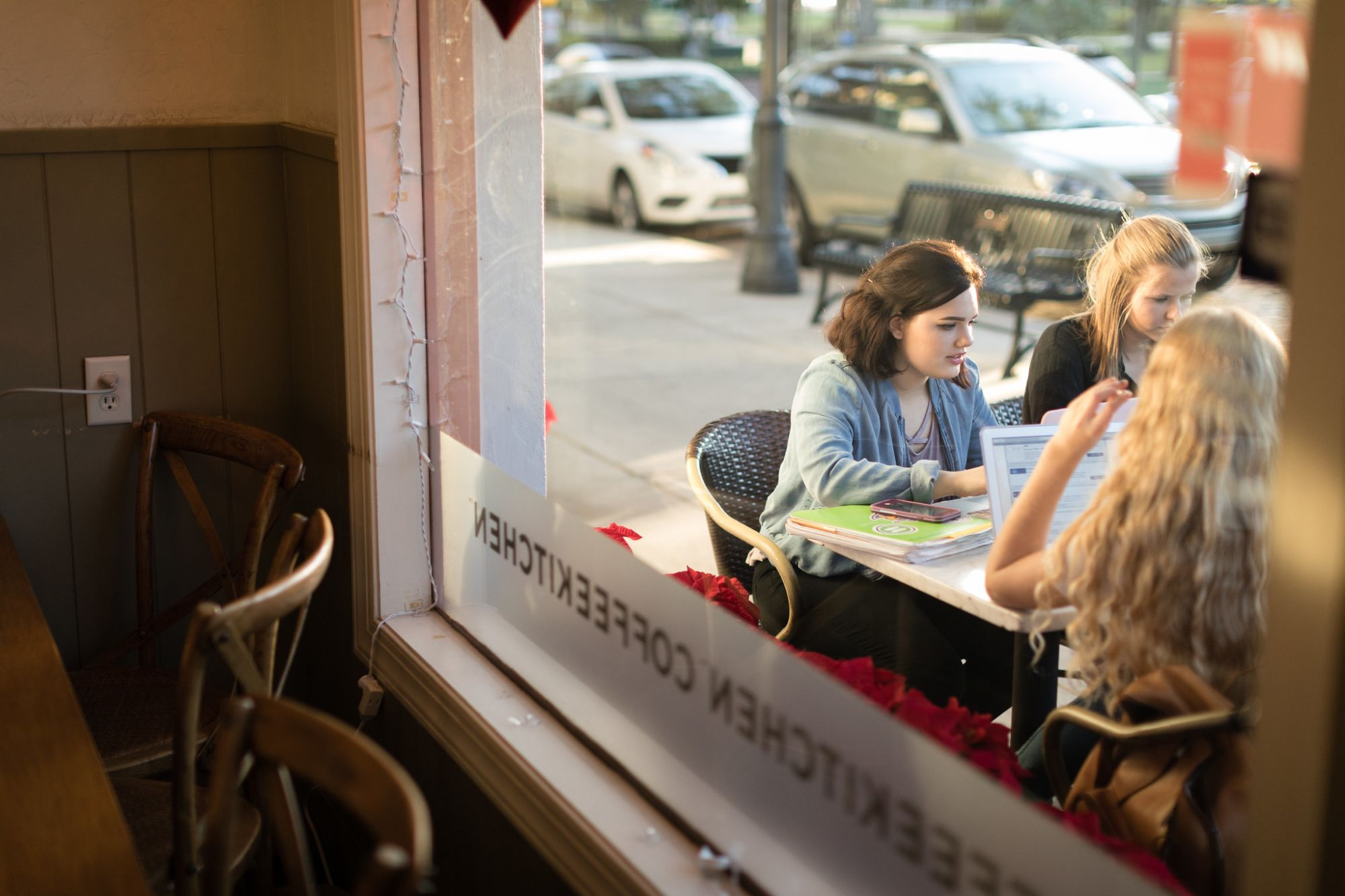 Students sit outside at Barnie's CoffeeKitchen collaborating on blog content for the company's website.