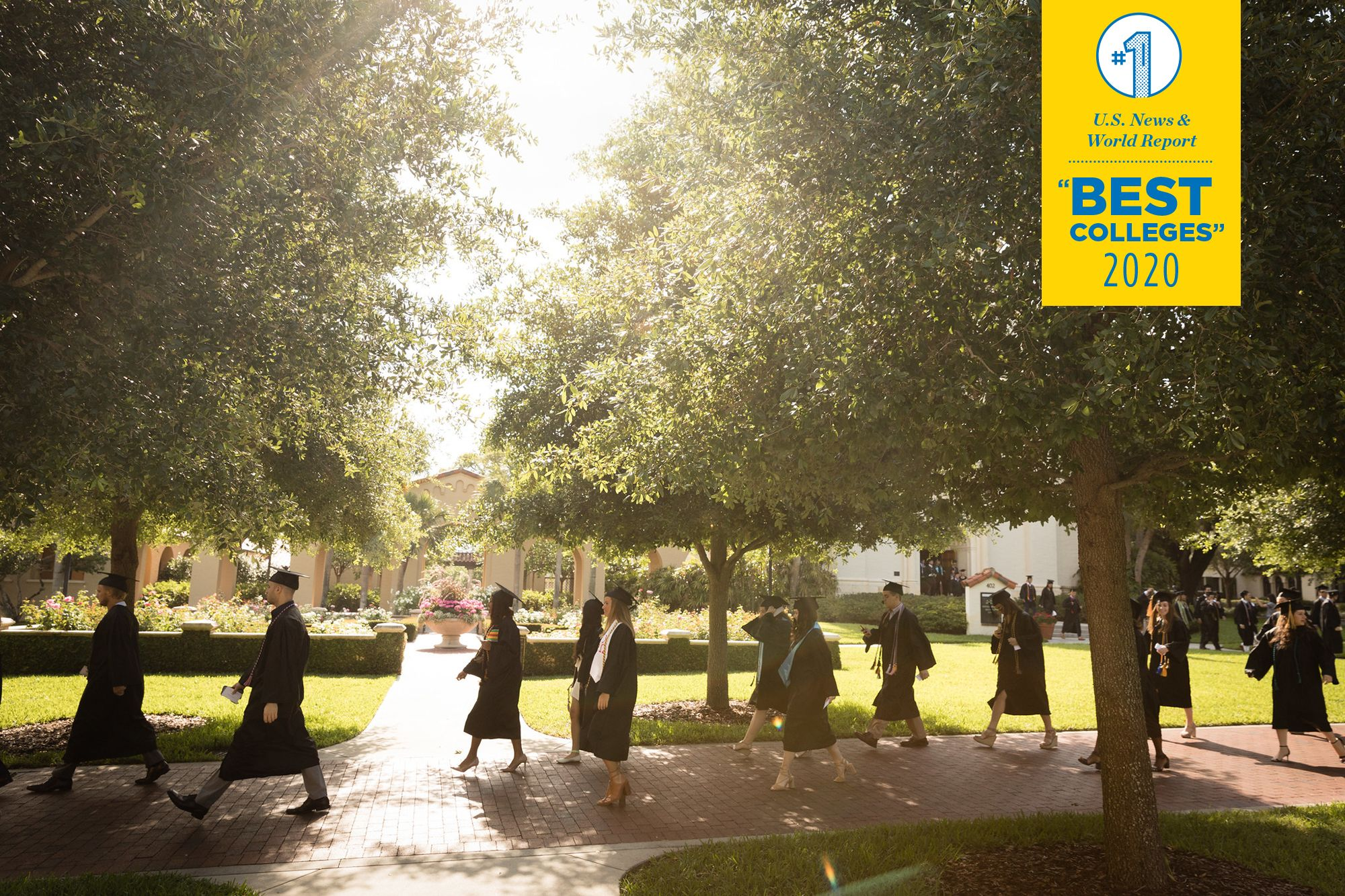 Rollins graduates walk past the iconic campus rose garden on their way to commencement.