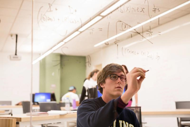 A student performs a math equation on a glass board.