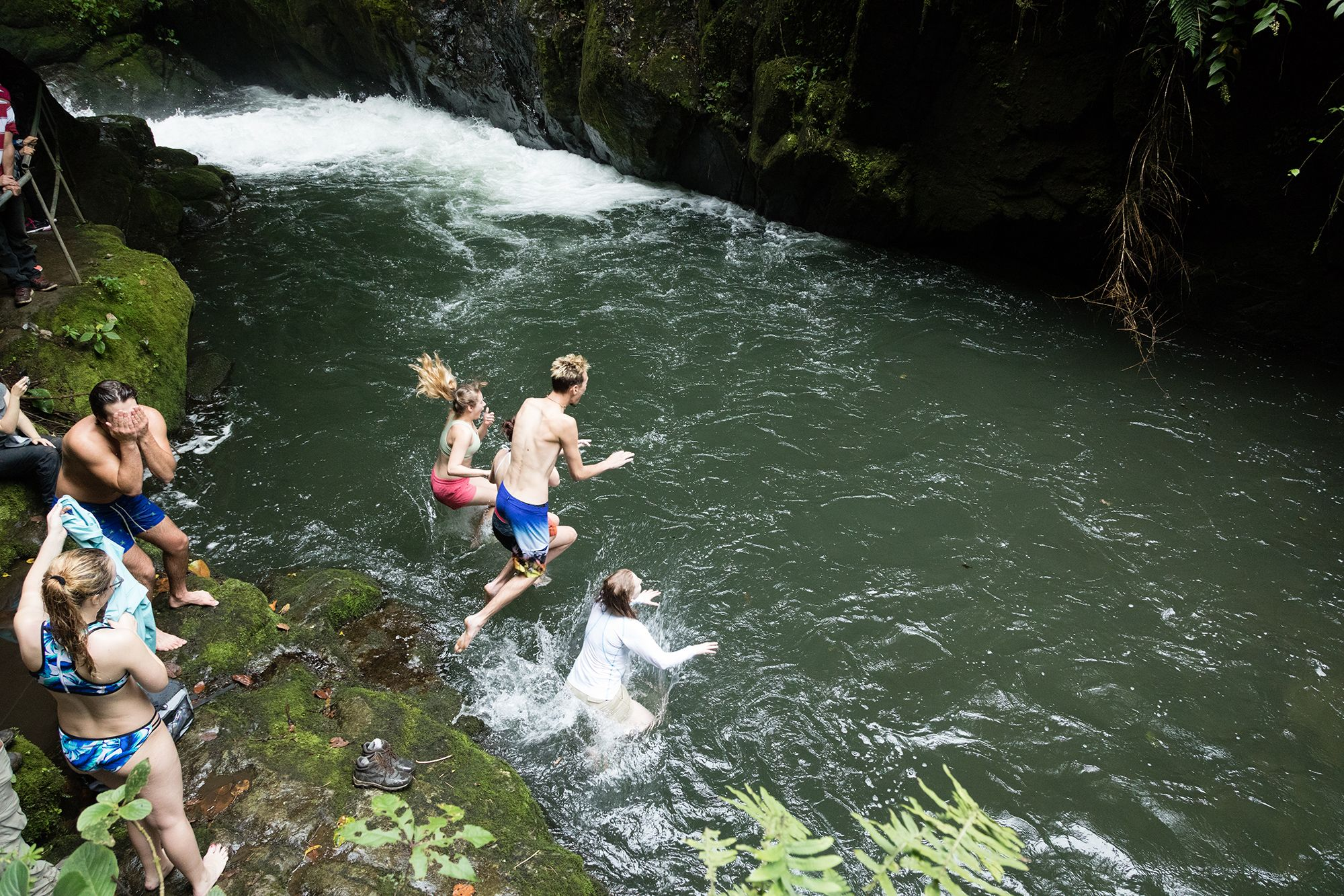 Students jumping from a cliff into the water in Costa Rica.