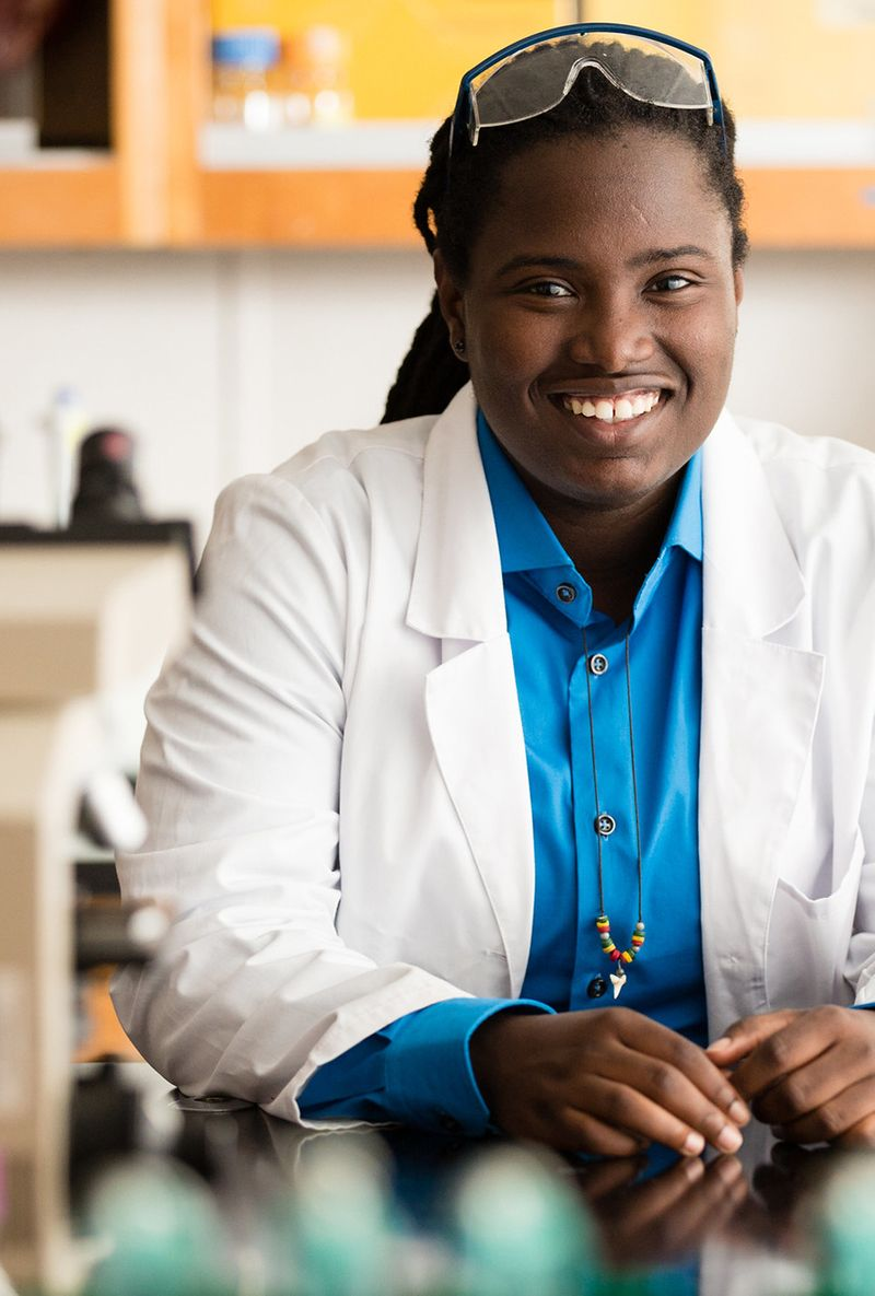 A biochemistry student poses for a portrait in a lab.