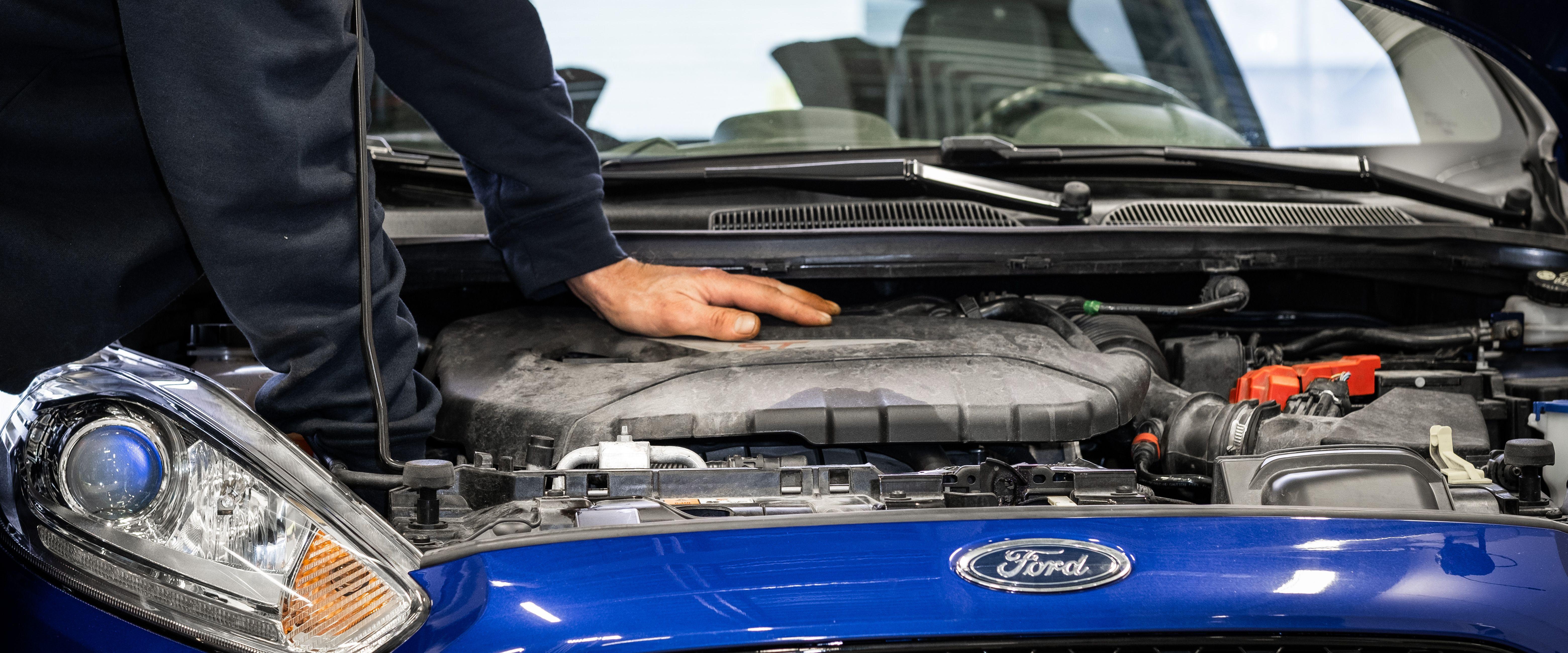 Mekaniker som skrur på motoren på en Ford