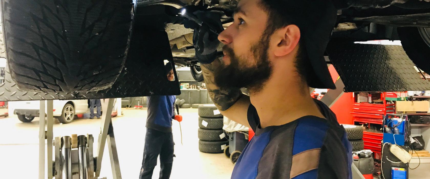 Illustrasjonsbilde av en mekaniker som skrur i motoren på en bil