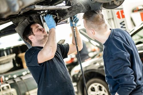 Illustrasjonsbilde av mekanikere som reparerer understellet på en bil
