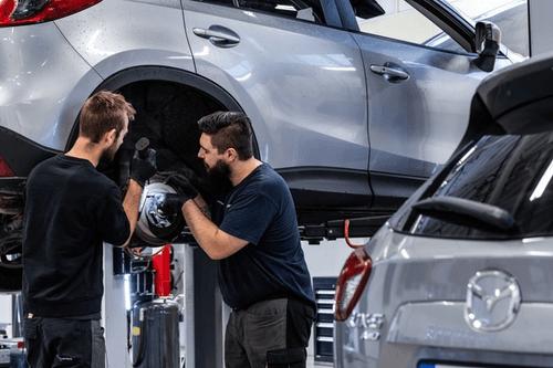 Illustrasjonsbilde av to mekanikere som jobber på en Mazda